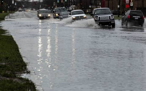 Cars drive through floodwaters on Avenue O in Chicago.