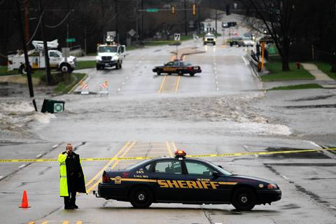 A DuPage County Sheriff's officer blocks Maple Avenue as the DuPage River flows over the roadway in Lisle.