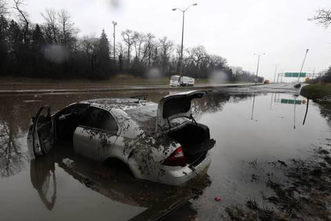 A Ford is revealed as the water recedes at Pratt Avenue and the Edens Expressway.