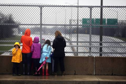 Spectators watch from the overpass at Pratt Avenue at the flooding on the Edens Expressway