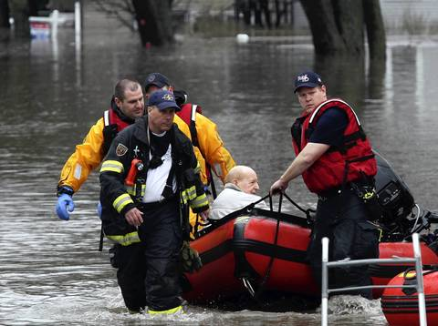 Ed Linchester, 93, is pulled into dry land by firefighters after being evacuated in Lisle.