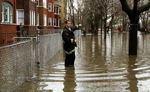 Chicago firefighter Tom Rogala stands in knee deep water in the 4900 block of north St. Louis Avenue as members of the CFD check on residents.