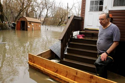 Bob Decremer's stands behind his homemade wooden dam around his home to keep water out. His home is next to the river in the Albany Park neighborhood.