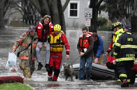 A woman is carried to dry land after being evacuated in Lisle. Bill Smith walks through the water with his dog.