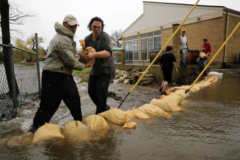 In Des Plaines, Bob Benson, left, and Anthony Gonka and others sandbag behind Gonka's home (background), trying to prevent the Des Plaines River from flooding into Shagbark Lake. Gonka's home backs up to the lake.