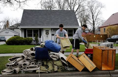 Bobby Mueller, 16, left, and his friend Nick Fornatto place wet carpet out in the curb after Mueller's basement was flooded in Elmhurst.