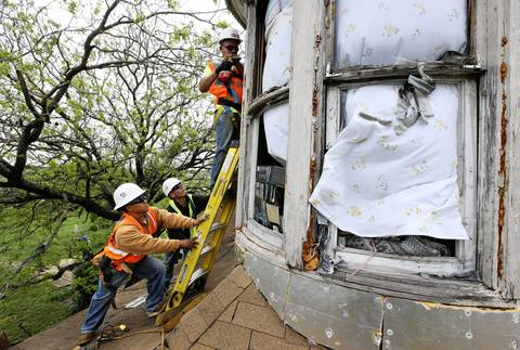 Workers with Johnson Roofing cover up the window frames of Carol Anne Kocian's home with sheets of plywood in West, Texas. Kocian lives very close to the site of the deadly fertilizer plant explosion that blew out all the windows of her house.