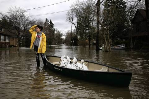 Ewelina Wiszowata, 22, waits for her boyfriend to help move sandbags on Hawthorne Lane, flooded by the rising Des Plaines River, in Des Plaines.