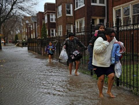 Juana Garcia carries her two-year-old daughter, Haidy, as her other children Edwin, 11, and America, 7, walk behind her through a flooded 4900 block of North Drake Avenue in Chicago.