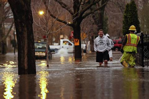 Ben Anderson, left, laughs while walking through flood waters in the 4900 block of North Drake Avenue in Chicago.