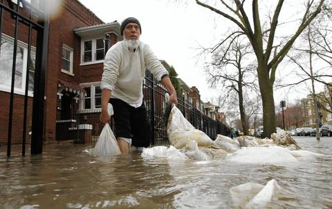 Yaqub Patel grabs sand bags from the front of his home in the 4900 block of N. Drake Ave. to block rising water from reaching his foundation.