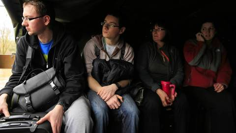 Arek Fejklowicz, 26, left, rides with friends being evacuated from their home along Big Bend Drive in Des Plaines. The area was flooded by the rising Des Plaines River.