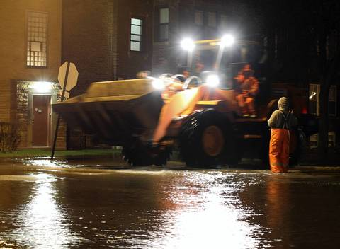 A tractor used to haul piles of sand moves south at the flooded corner of Avers and Carmen Avenues.