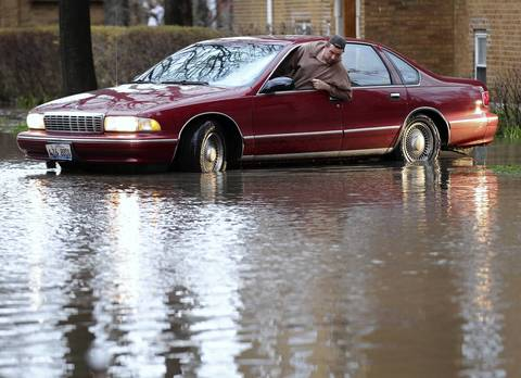 Dan Schlesner navigates his car through a flooded 3300 block of West Carmen Avenue.