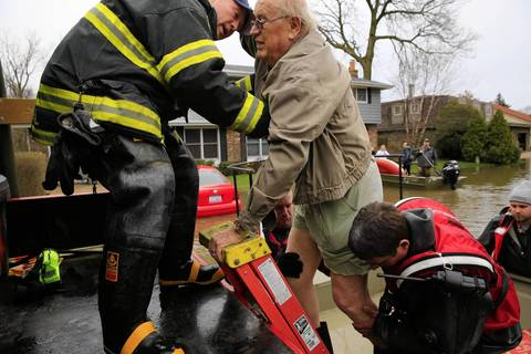 Fred Becker, 78, is helped by Des Plaines firefighters and Cook County Forest Preserve officers. Becker, along with his wife, had to be evacuated after his home on Big Bend Drive in Des Plaines became flooded by the rising Des Plaines River.