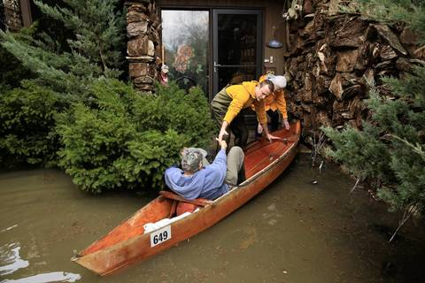 Walter Kuhn, 95, from left, is delivered by canoe with help from his grandson John Kirpanos and friend Tricia Garrity, 77, to the home of Kuhn's daughter after Kuhn evacuated his home on Big Bend Drive which was flooded by the rising Des Plaines River in Des Plaines.