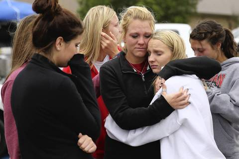 West High School senior students Kelsey Hoelscher, center, and Heather Perry, right, embrace after praying for the victims and survivors the day after the West Fertilizer Company explosion in West, Texas. Hoelscher's uncles, Bob Snokhous and Doug Snokhous, were volunteer fire fighters who are presumed dead after the fertilizer company caught fire and exploded, injuring more than 160 people and leaving damaged buildings for blocks in every direction.
