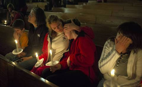 People mourn during a candlelight vigil at St. Mary's Assumption Catholic Church in West, Texas for victims of a fertilizer plant explosion in the town of West, Texas. Among the 14 dead are four emergency medical technicians who rushed to the fertilizer plant to put out a fire.