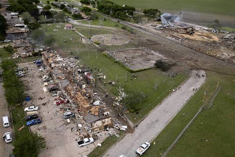 Search and rescue workers comb through what remains of a 50-unit apartment building, on left, the day after an explosion at the West Fertilizer Company, top right, destroyed the building in West, Texas.