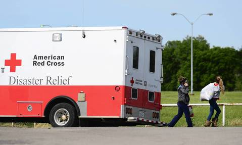 Residents carry their belongings past an American Red Cross Disaster Relief truck parked on a road leading to the fertilizer plant where a massive blast took place the night before in West, Texas.