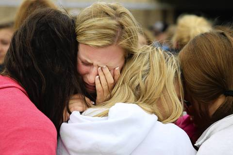 West High School senior Mackenzie Wernet, center, is embraced by fellow students and friends after praying for the victims and survivors the day after the West Fertilizer Company explosion in West, Texas. Wernet's home was destroyed when the fertilizer company caught fire and exploded.