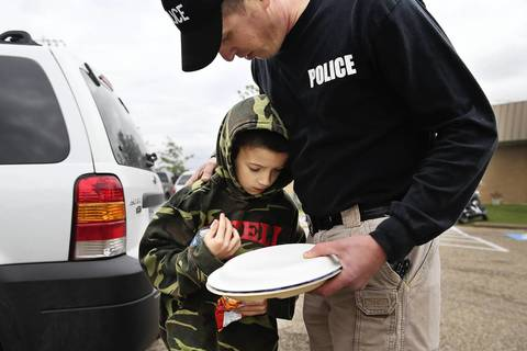 Hewitt, Texas police officer Mike Zahirniak, right, comforts his son, Coy Zahirniak, 9, outside the West Community Center the day after the West Fertilizer Company explosion in West, Texas. Coy alerted his family to the fire across the street from his grandfather Willie Zahirniak's home and the plant exploded as they evacuated. The home was destroyed and Coy has been credited for saving his family from harm.