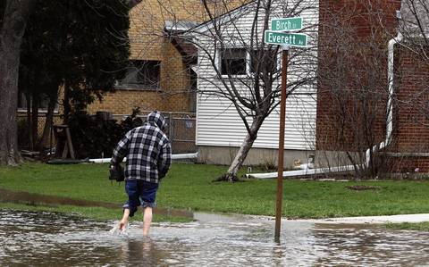 Rigoberto Cortez carries his shoes to protect them from the flooded streets as he goes to check on his brother-in-law's home near Everett Avenue and Birch Street in Des Plaines.