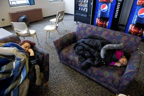 Sarah DaSilva, left, and her daughter Marianna, 5, of Maywood, sleep at a Red Cross shelter inside a student center at Benedictine University in Lisle.