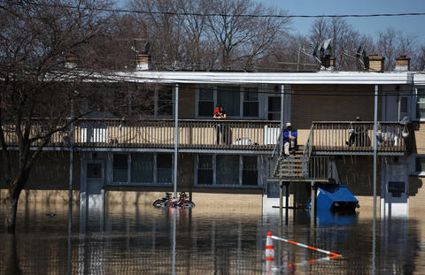 Residents watch the water from an apartment complex near downtown Des Plaines on Saturday. The river is not expected to recede until Sunday, according to a Des Plaines firefighter.