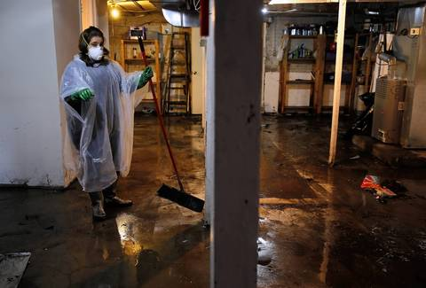 A woman cleans her mother's basement which flooded with about three feet of water on Drake Avenue, in the Albany Park neighborhood of Chicago, south of the Chicago River.