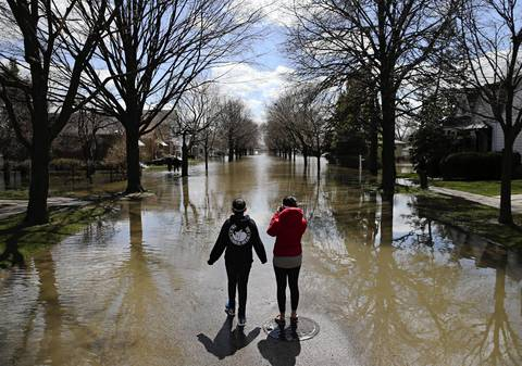 Mariela, 12 and Mia Nevarez, 14, watch as their father Alex Nevarez wades back to their flooded home to retrieve belongings in the 4500 block of Grove Avenue in Forest View.