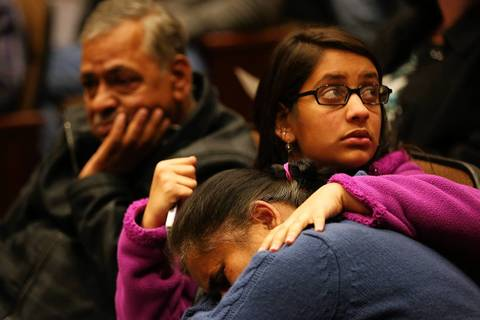 A Lisle resident is comforted after she became emotional speaking about the damage to her family's home during an emergency village board meeting in the aftermath of this week's flooding.