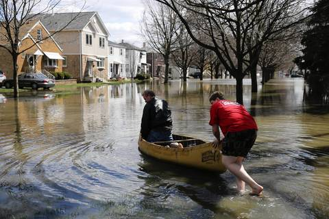 Larry and Joseph Powell, 16, canoe along the 4500 block of Grove Street back to their flooded home in Forest View.