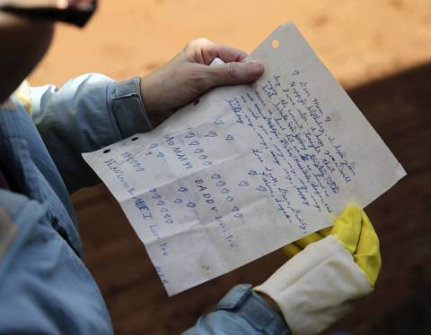 Marge Bouma finds a soggy birthday letter that her children wrote her in 1977 while cleaning out her flooded basement in Forest View. Marge Bouma said she had lived in the home for 47 years and had never had a drop of water inside until this week.