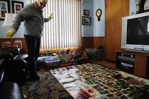 Marge Bouma dries hundreds of family photographs while cleaning out her flooded basement in Forest View. Bouma said she had lived in the home for 47 years and had never had a drop of water inside until this week.