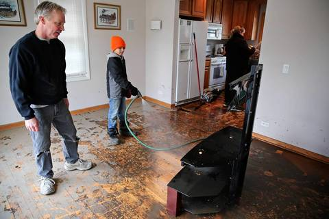 Lou Laroche watches as his nephew, Kevin Laroche, 12, used a hose to spray mud off his television stand while they worked to clean up in the aftermath of this week's flooding on Dumoulin Avenue in Lisle, Ill.
