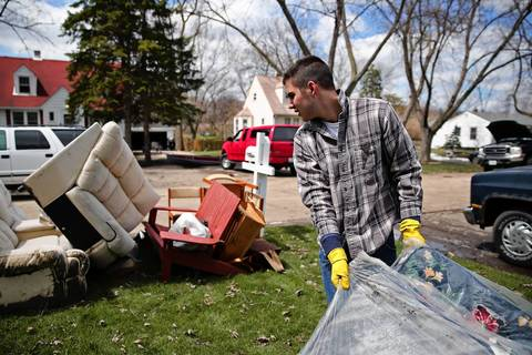 Wally Kuptz drages a ruined mattress to the curb as he helped his uncle, Lou Laroche, clean up in the aftermath of this week's flooding Saturday, April 20, 2013 on Dumoulin Avenue in Lisle, Ill.