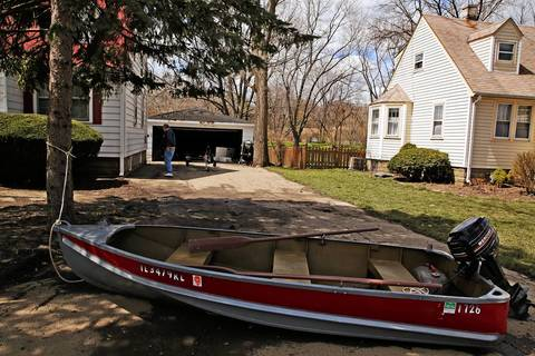 A boat, still tied to a tree to keep it from floating away, sits in the driveway as property owner Fred Malayter uses a marker to draw the water line on the exterior of his rental property while he other area residents worked to clean up in the aftermath of this week's flooding on Dumoulin Avenue in Lisle, Ill.