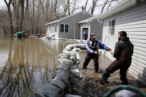 Kasey Kusch (left) and Aaron Dullum pile sandbags around their grandfather's home on West Riverside Drive in the Orchard Heights subdivision in unincorporated McHenry Township on Sunday. The entire subdivision was partially submerged with flood water.