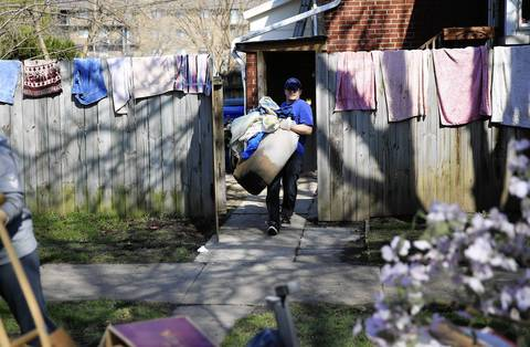 Doug Scott carries out water soaked belongings to the curb outside her families home on Oakwood Avenue near White Street in Des Plaines. Towels hang dry on the fence. They initially tried to stop the water with the towels.