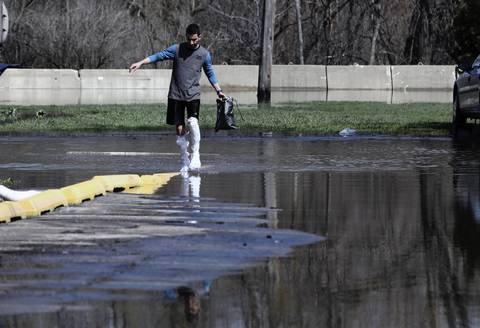 Ahmed Makki, 22, wears trash bags as shoes to cross a parking lot filled with water so he can get from his apartment to his car in Des Plaines off of Oakwood Avenue near River Road.