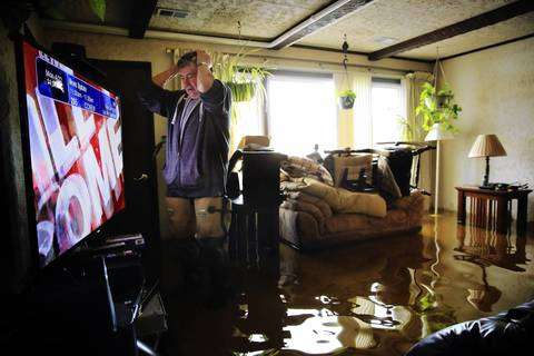 """Ron Madon, 74, turns on the news Monday in the living room of his home that was flooded by recent heavy rains on Knollwood Road in Fox Lake. """"It's all about Boston,"""" he lamented, hoping for news about flood crests along the Fox River."""