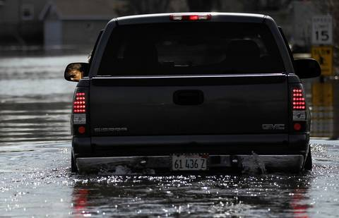 Ron Madon, 74, checks the water depth around his truck as he returns to his home that has been flooded by recent heavy rains on Knollwood Road in Fox Lake.