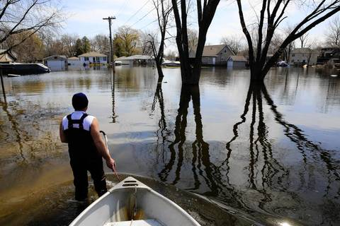 John Annarella, 47, returns a boa to the flooded Fox Lake home of his brother-in-law Dave Marino, whom Annarella was helping pump water from the house on Oak Lane.