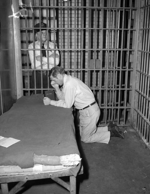 "George Lettrich Jr., who was sentenced to die for the murder of Roberta Rinearson, prays in his cell as guard Frank De Lucas watches on March 6, 1952. Lettrich was scheduled to die via the electric chair on Jan. 19, 1952, but was granted a stay by the Supreme Court. He was later exonerated when the high court found there was ""not a scintilla of evidence"" to connect him with the crime."