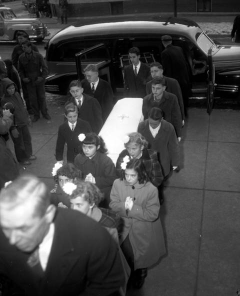 Schoolmates from St. Barbara Catholic School in Brookfield act as pall bearers carrying the casket of Roberta Rinearson into Our Lady of the Angels Catholic Church for her funeral on Dec. 22, 1948.