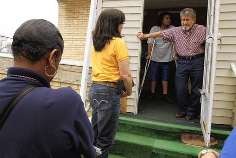 Vicente Gutierrez (right) and his grandson Tony, 19, (behind) answer questions by Janet Pate (center) of IEMA and Carolyn Robinson-Tucker (left) of FEMA as local, state and federal officials were in the Albany Park neighborhood today assessing flood damage of homeowners and apartment dwellers.