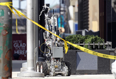 A robot retrieves a suspicious package tied to a flagpole on the 400 block of North Michigan Avenue Tuesday.