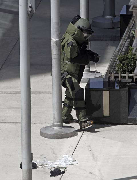 A member of the Chicago Police Bomb and Arson Unit dismantles the components of a suspicious package tied to a flagpole on the 400 block of North Michigan Avenue.