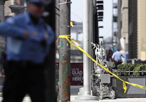 A robot retrieves a suspicious package tied to a flagpole on the 400 block of North Michigan Avenue.